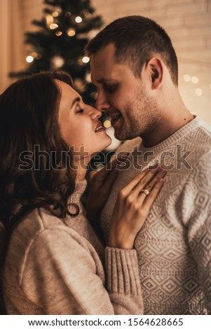 Lovely couple in sweaters hugging and celebrating new year in front of Christmas tree in decorated interior. #1564628665
