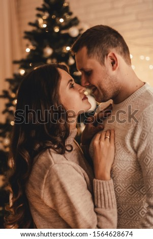 Lovely couple in sweaters hugging and celebrating new year in front of Christmas tree in decorated interior. #1564628674