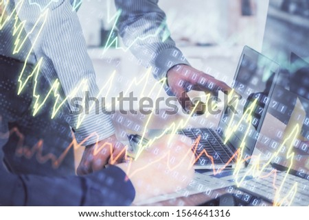 Double exposure of graph with man typing on computer in office on background. Concept of hard work. Closeup. #1564641316