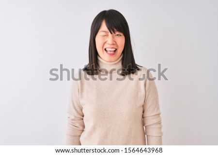 Young beautiful chinese woman wearing turtleneck sweater over isolated white background winking looking at the camera with sexy expression, cheerful and happy face. #1564643968