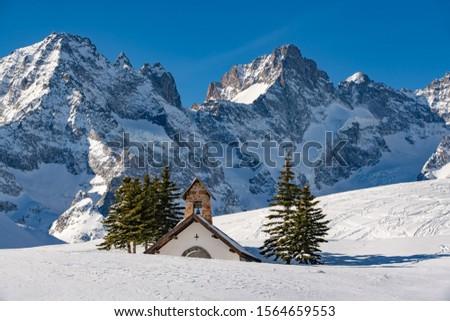 Winter view on the glaciers and mountain peaks of the Ecrins National Park (Pic Gaspard) with La Chappelle des Fusillés. Col du Lautaret, Hautes-Alpes, Alps, France