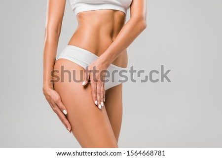 cropped view of beautiful slim woman in underwear touching leg isolated on grey Royalty-Free Stock Photo #1564668781
