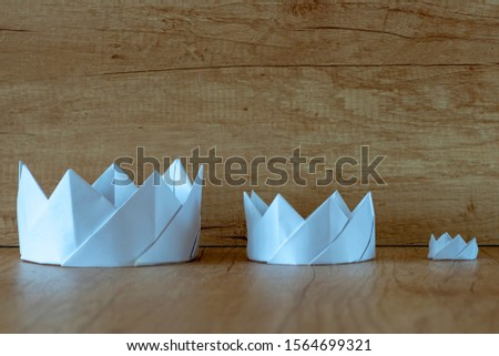 Paper crown. Three paper white crowns. Royal family, royal dynasty concept