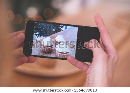Woman taking picture of Christmas cupcakes on her smartphone