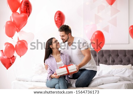 Young man presenting gift to his girlfriend in bedroom decorated with heart shaped balloons. Valentine's day celebration #1564736173