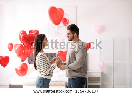 Lovely young couple in bedroom decorated with heart shaped balloons. Valentine's day celebration #1564736197