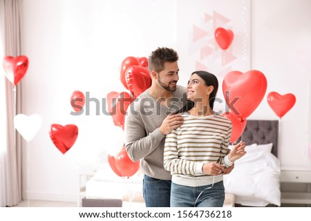 Lovely young couple in bedroom decorated with heart shaped balloons. Valentine's day celebration #1564736218