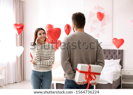 Young man presenting gift to his girlfriend in bedroom decorated with heart shaped balloons. Valentine's day celebration #1564736224