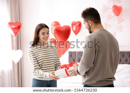 Young man presenting gift to his girlfriend in bedroom decorated with heart shaped balloons. Valentine's day celebration #1564736230