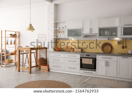 Modern kitchen interior with stylish wooden table Royalty-Free Stock Photo #1564762933