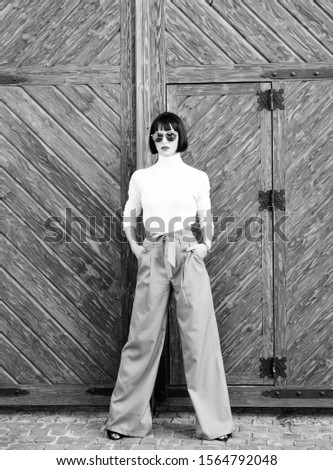 Girl wear loose high waisted pants. Fashion shop. High waisted pants fashion trend. High waisted trousers. Woman attractive brunette wear fashionable clothes. Femininity and emphasize feminine figure. #1564792048