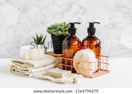 Soap and shampoo bottles and cotton towels with green plant on white table inside a bathroom background. Royalty-Free Stock Photo #1564796479