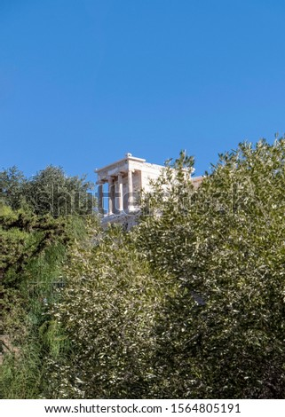 distant view of Athena Nike ancient temple between trees and clear blue sky, Athens Greece #1564805191