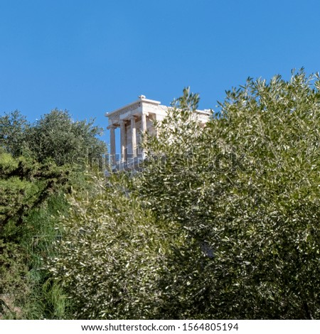 distant view of Athena Nike ancient temple between trees and clear blue sky, Athens Greece #1564805194