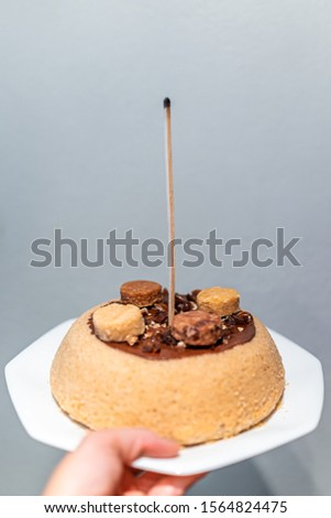 Hand holding one yellow vanilla dessert homemade sponge cake with chocolate frosting and macaroon decoration with candle match stick for birthday #1564824475