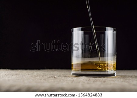 whiskey is poured into a glass #1564824883