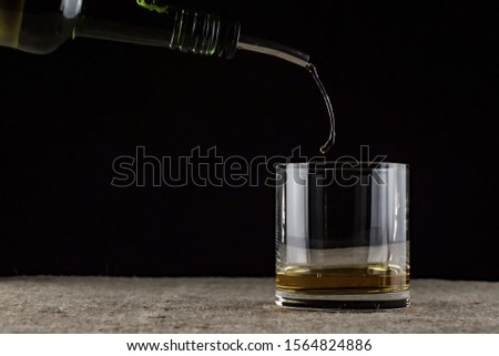 whiskey is poured into a glass #1564824886