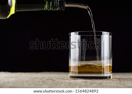 whiskey is poured into a glass #1564824892