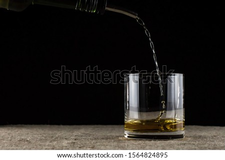 whiskey is poured into a glass #1564824895