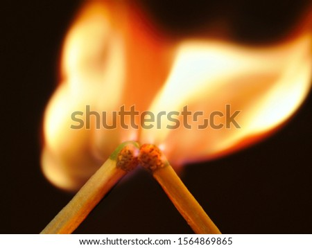 Photo two adjacent matches burn brightly. Dark background, bright flame #1564869865