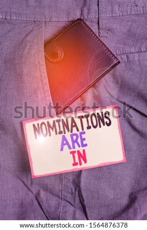 Conceptual hand writing showing Nominations Are In. Business photo showcasing Formally Choosing someone Official Candidate for an Award Small wallet inside trouser front pocket near notation paper. #1564876378