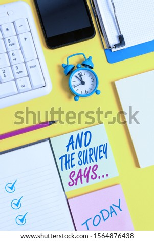 Writing note showing And The Survey Says. Business photo showcasing doing poll and bring the results discuss with others White paper with copy space with paper clips clock and pc keyboard. #1564876438