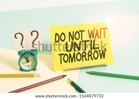 Text sign showing Do Not Wait Until Tomorrow. Conceptual photo needed to do it right away Urgent Better do now Mini size alarm clock beside stationary placed tilted on pastel backdrop. #1564879732