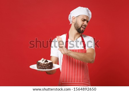 Bearded male chef cook or baker man in striped apron white t-shirt toque chefs hat posing isolated on red background. Cooking food concept. Mock up copy space. Showing stop gesture to plate with cake #1564892650
