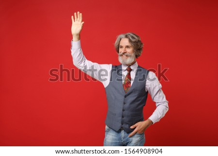 Elderly gray-haired mustache bearded man in classic shirt vest colorful tie isolated on red background. People lifestyle concept. Mock up copy space. Waving and greeting with hand as notices someone #1564908904