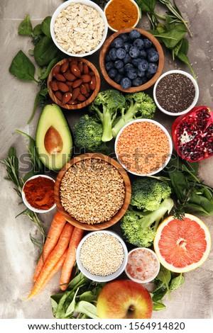 Healthy food clean eating selection: fruit, vegetable, seeds, superfood, cereals, leaf vegetable on background #1564914820