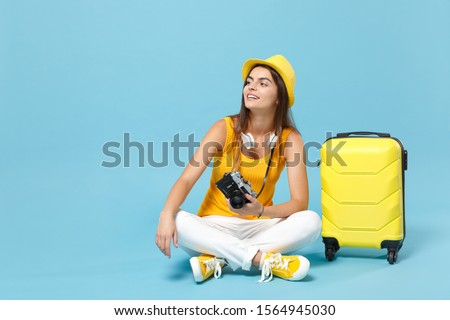 Traveler tourist woman in yellow casual clothes hat with suitcase photo camera isolated on blue background. Female passenger traveling abroad to travel on weekends getaway. Air flight journey concept #1564945030