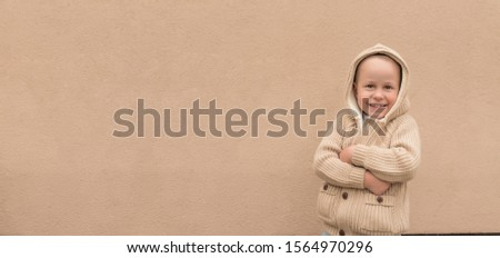 Little boy 3-5 years old, beige sweater with hood, happy smiling, cheerful joyful. Free space for text. Background wall, autumn on street. Emotions pleasure fun. Holiday birthday concept #1564970296