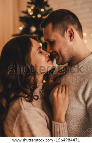Lovely couple in sweaters hugging and celebrating new year in front of Christmas tree in decorated interior. #1564984471