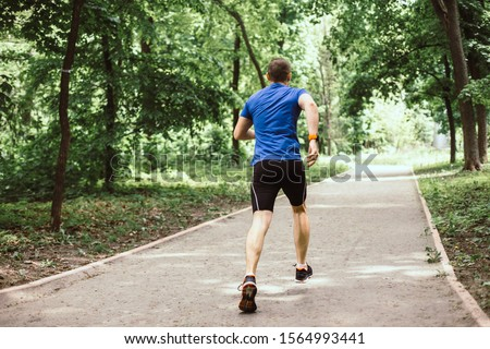 Man is running in the urban park or forest #1564993441