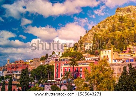 Panoramic view on the pictoresque town of Taormina, Sicily, Italy. Houses and resorts on the hill with beautiful scenery of trees, rocks, and clouds. #1565043271