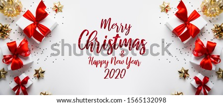 Merry Christmas and Happy Holidays greeting card, frame, banner. New Year. Noel. Christmas gifts and red, golden decor on white background top view. Winter xmas holiday theme. Flat lay Royalty-Free Stock Photo #1565132098
