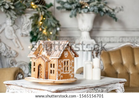 Postcard gingerbread house. Defocused lights of Christmas tree. Holiday mood. Christmas and Happy new year. #1565156701