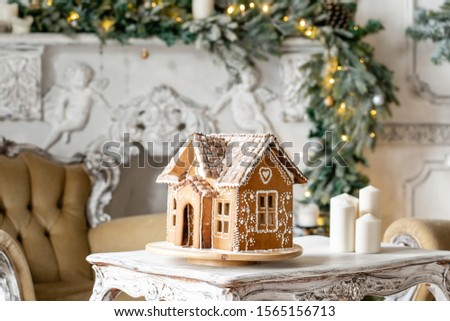 Postcard gingerbread house. Defocused lights of Christmas tree. Holiday mood. Christmas and Happy new year. #1565156713