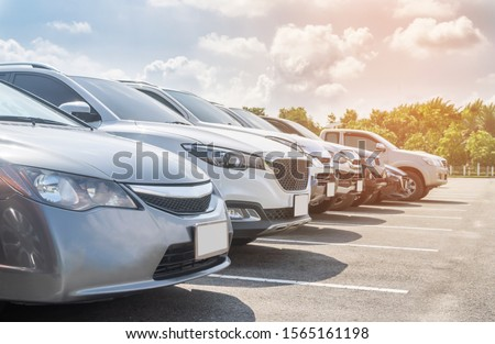 Front view car parking in asphalt parking lot in a row with white cloud and blue sky background. Outdoor parking lot with fresh ozone and green environment of travel transportation technology concept #1565161198