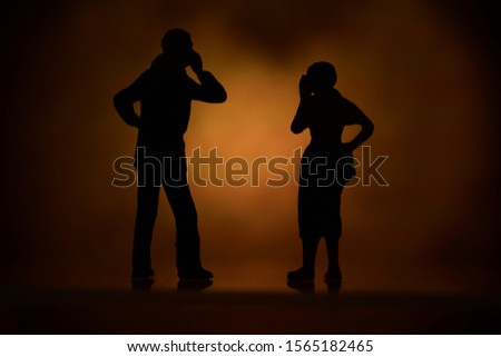 Silhouette man and woman standing, talking with a mobile phone Royalty-Free Stock Photo #1565182465