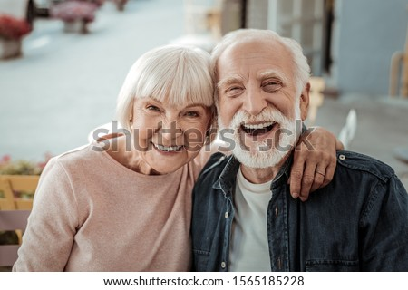 Elderly couple. Joyful nice elderly couple smiling while being in a great mood #1565185228