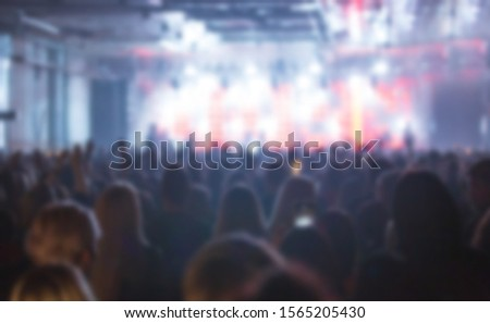Blurred concert background with group of music fans partying to famous musical band performing on stage.Blurry festival back ground with bright lights and silhouette of people on dance floor