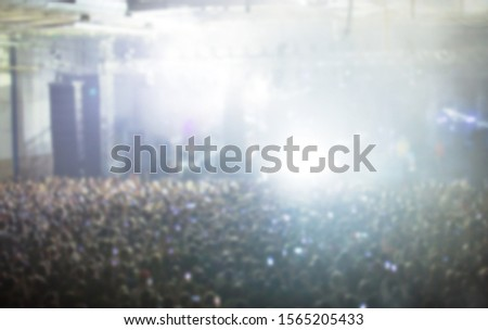 Blurred concert background with group of music fans partying on dance floor in arena night club.Rock show in musical hall.Out of focus image for entertainment event poster