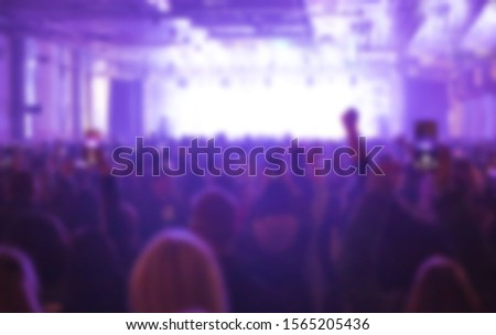 Blurred concert background with group of music fans partying to favorite musician performing live set on stage in bright lights.Out of focus image for musical festival poster