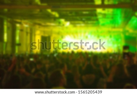 Blurred concert background with music fans partying in night club on dance floor to famous dj set.Bright stage lights and vibrant green color.Blurry image with group of people for festival poster