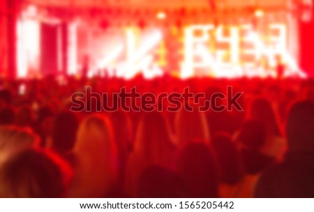 Blurred concert background with music fans partying on dance floor in bright red stage lights.Group of people in music hall listening to famous musician performing live set.Blurry image for poster