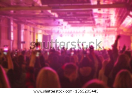 Blurred concert background with group of music fans partying in huge night club.Bright stage lights illumination and red color.Blurry poster for edm festival event