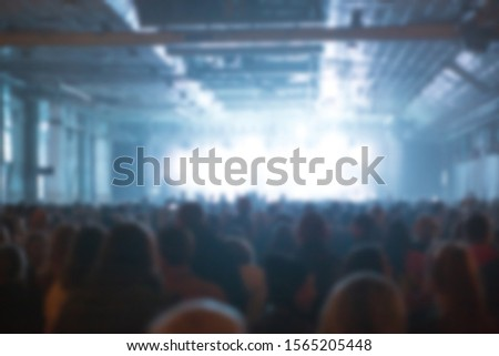 Blurred concert background with group of fans partying on edm music festival in night club.Silhouette of people in bright stage lights.Out of focus image for entertainment event poster