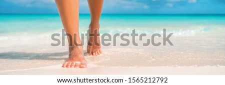 Woman feet walking on caribbean beach barefoot closeup of foot coming out of water after swim banner panorama. Honeymoon travel vacation, #1565212792