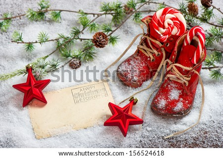 vintage christmas decoration red stars, sweets and antique baby shoes over snow background. retro style picture with empty postcard for your text